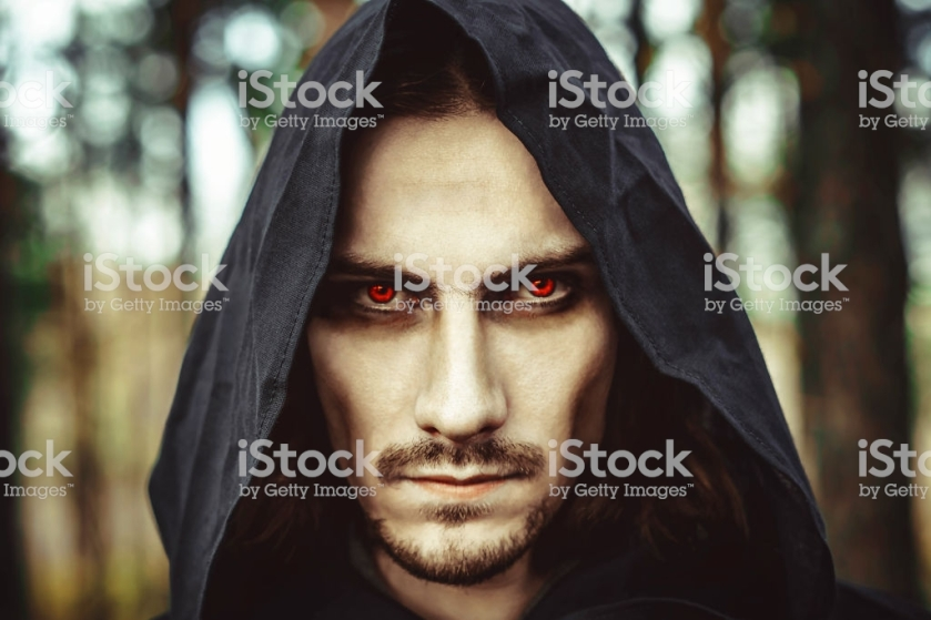 the vampire in the hood with glowing eyes in the forest